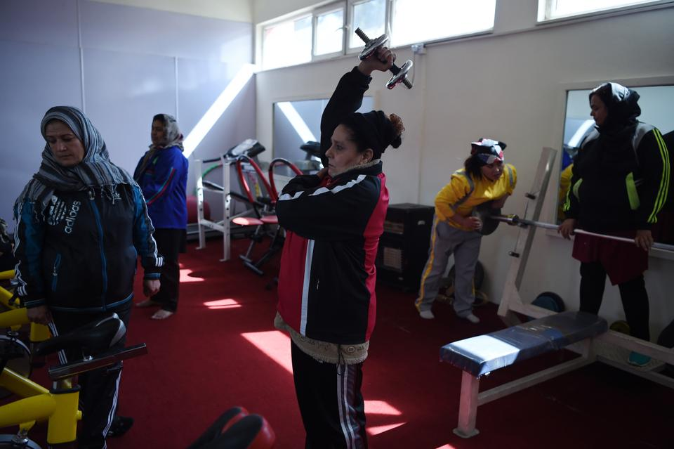Afghanistan national powerlifting team member Rasheda Parhiz (R), 40, takes part in a training session at a women's gym at Ghazi stadium in Kabul.