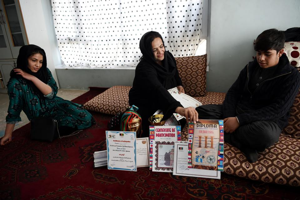 Afghanistan national powerlifting team member Rasheda Parhiz (C), 40, shows her trophies, medals and sport certificates to her daughter Lema (L) and son Shabir at her home in Kabul.