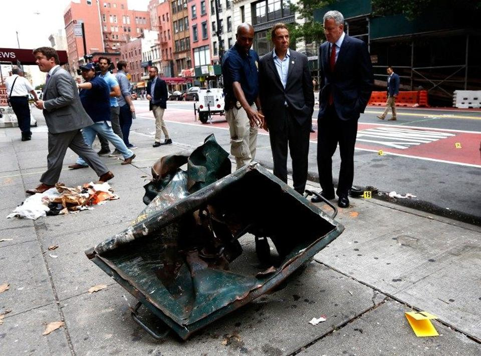 New York Mayor Bill de Blasio (2-R) and New York Governor Andrew Cuomo (3-R) stand in front of a mangled dumpster while touring the site of an explosion that occurred in the Chelsea neighborhood of New York on September 18, 2016.