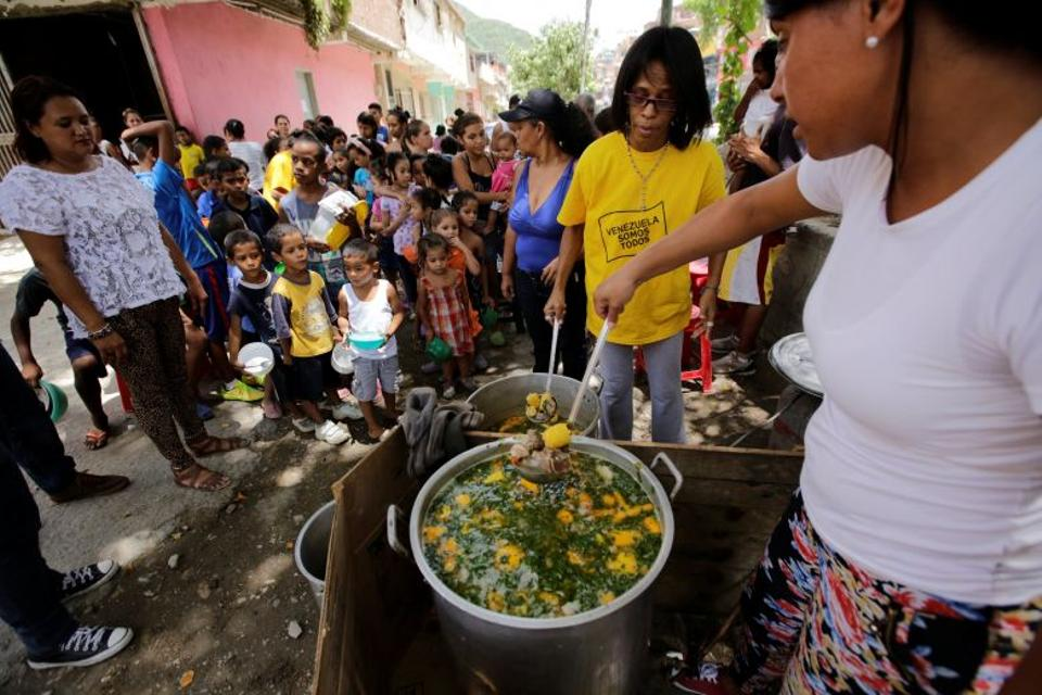 A volunteer prepares food to be distributed for free among residents on a street in the low-income neighborhood of Caucaguita near Caracas. Source: Reuters