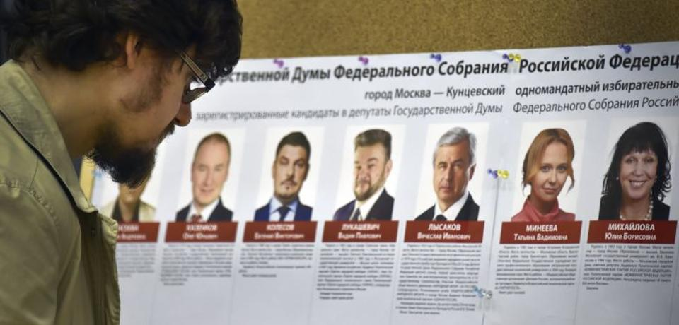 A man looks at an election poster with portraits of candidates at a polling station during parliamentary elections in Moscow on September 18, 2016. (AFP)