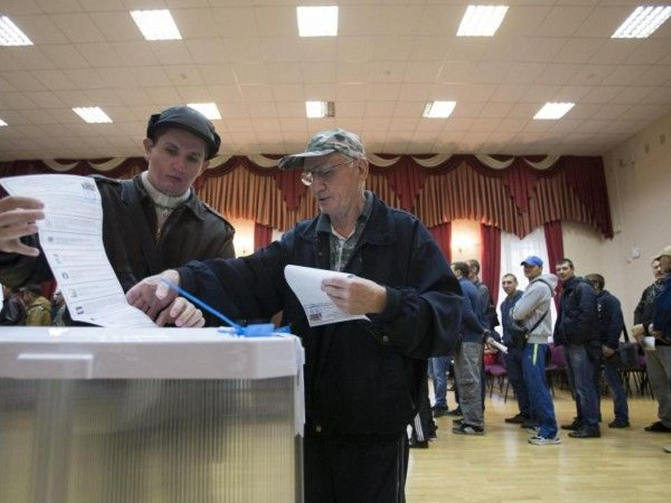 People cast their ballots at a polling station during parliamentary election in Moscow, Russia, Sunday, Sept. 18, 2016.