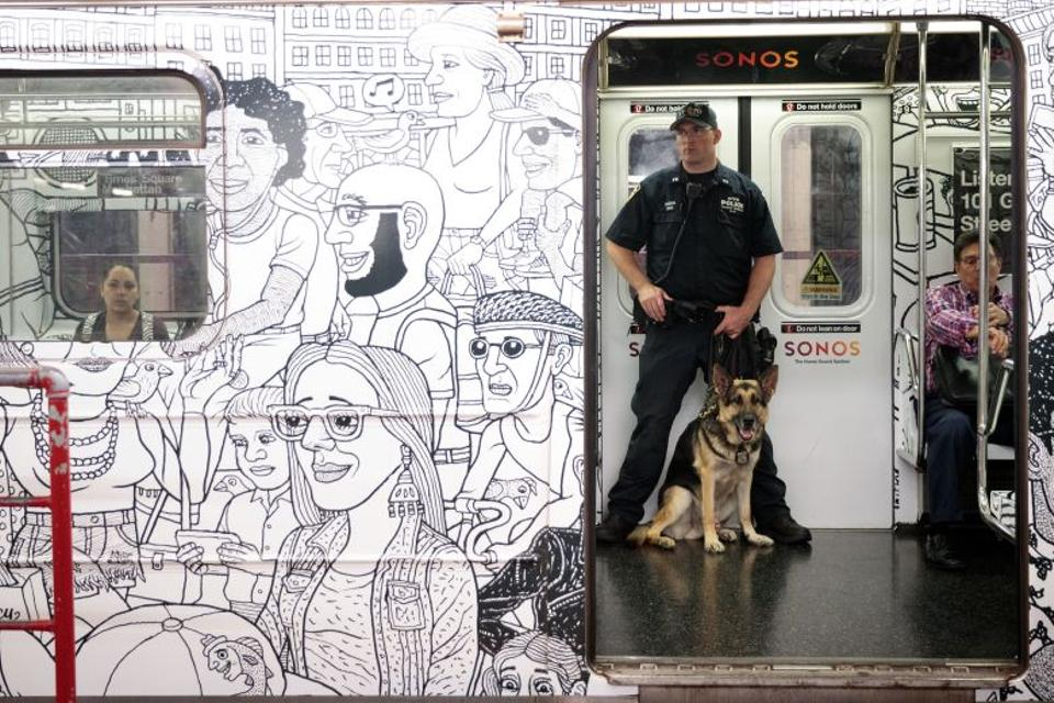 A member of the New York City Police Department K-9 Unit patrols on a subway train between Grand Central Terminal and Times Square, September 18, 2016 in New York City.
