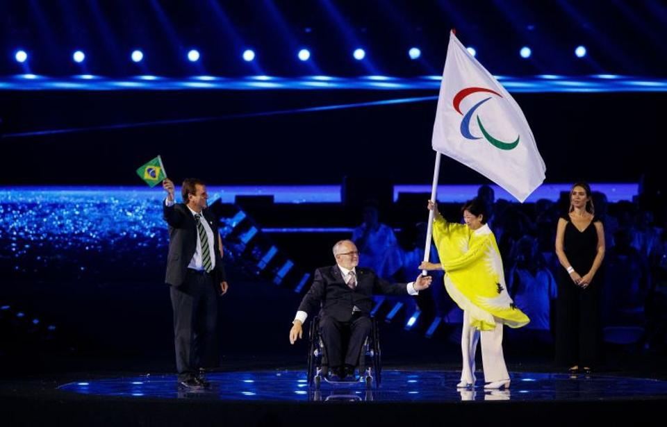 Eduardo Paes the Mayor of Rio de Janeiro applauds as Sir Philip Craven President of the IPC hands the Paralympic flag to the Governor of Tokyo Yuriko Koike during the closing ceremony of the Rio 2016 Paralympic Games.