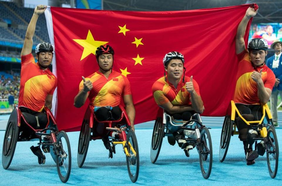 China's relay team pose with their country's national flag after winning the gold medal in the men's 4x400-meter - T53/54 final at the Olympic Stadium during the Paralympic Games.