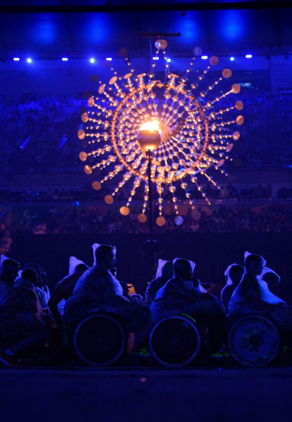 Members of the audience sit in front of the Paralympic Cauldron wrapped in plastic against the rain during the closing ceremony of the Rio 2016 Paralympic Games.