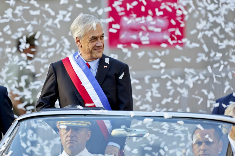 Chile's President Sebastian Pinera is showered with confetti as he rides in an open car to La Moneda presidential palace on the day of his inauguration in Santiago, Chile.