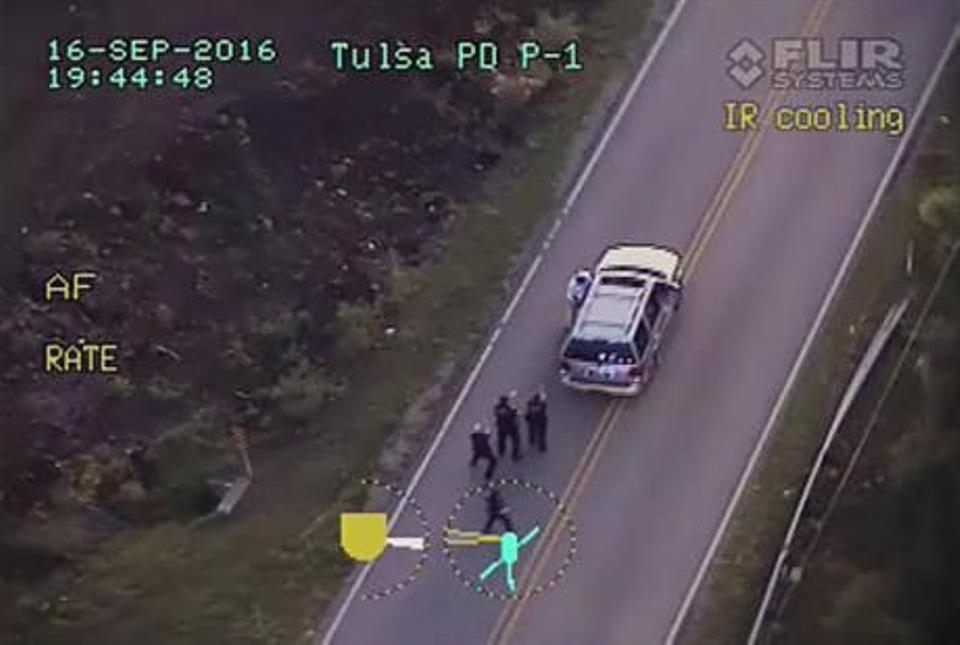 In this image made from a Friday, Sept. 16, 2016 police helicopter video, Terence Crutcher, top, is pursued by police officers as he walk to an SUV in Tulsa, Okla.