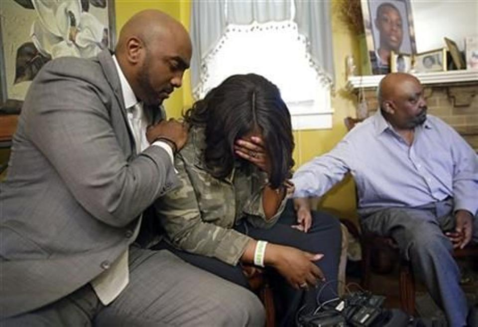 Attorney Damario Solomon-Simmons, left, comforts Tiffany Crutcher, twin sister of Terence Crutcher who was shot and killed by Tulsa Police Friday night Sept. 16, 2016. At right is Rev. Joey Crutcher, her and Terence's father.