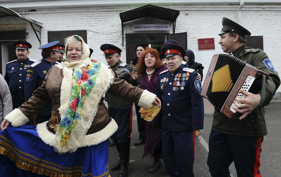 Members of a local Cossack community dance outside a polling station during the presidential election in Rostov-on-Don.