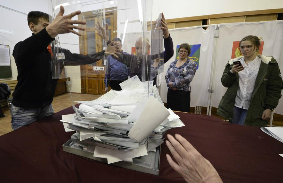 Members of a local election commission empty a ballot box before starting to count votes during the presidential election in the far eastern city of Vladivostok.