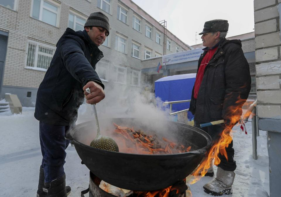 People cook a traditional meal near a polling station during the presidential election in Kazan, Russia.