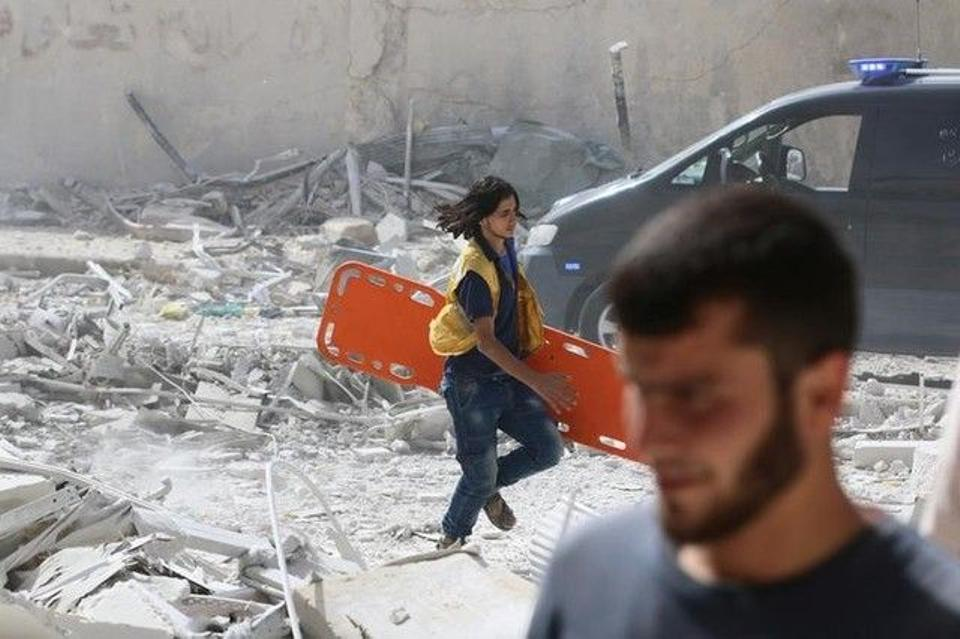 A man runs with a stretcher at a damaged site after air strikes on the opposition-held al-Qaterji neighbourhood of Aleppo, Syria September 21, 2016.