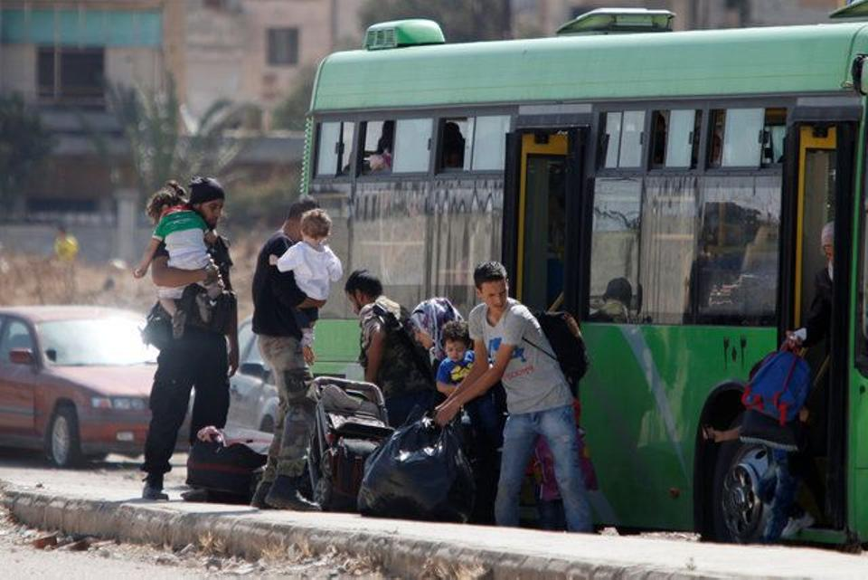 Families carry their luggage into a bus to evacuate the besieged district of Waer in the central Syrian city of Homs, after a local agreement reached between opposition forces and Syrian regime military forces, September 22, 2016.
