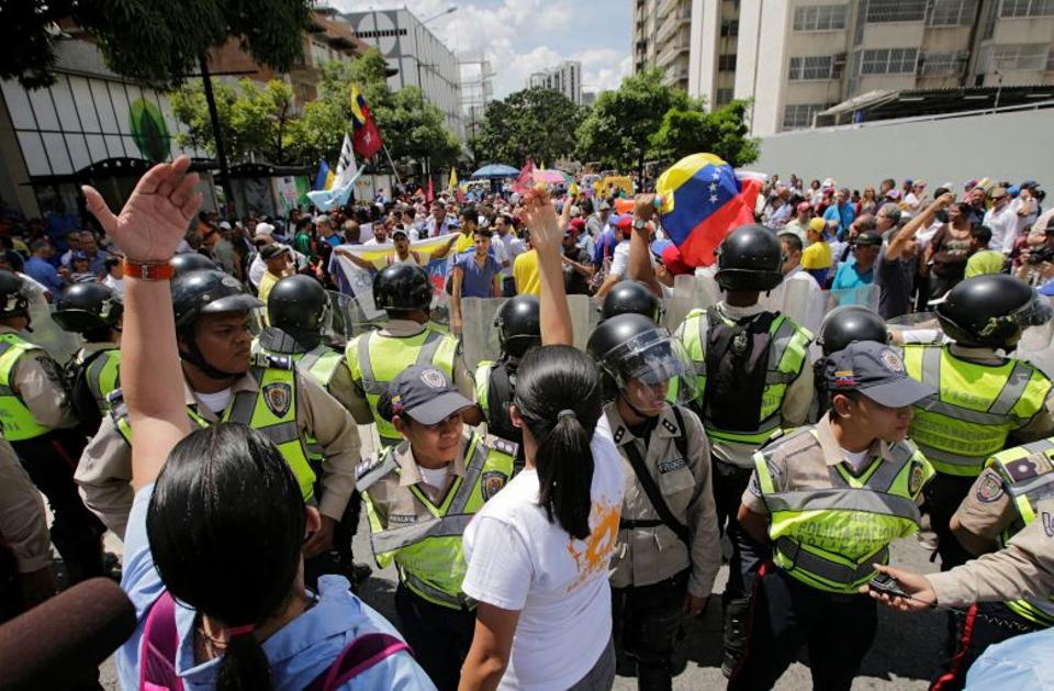 Supporters of Venezuela's opposition face police officers who are blocking a street, as they take part in a rally to demand a referendum to remove Venezuela's President Nicolas Maduro from power, in Caracas, Venezuela, September 16, 2016. (Reuters)