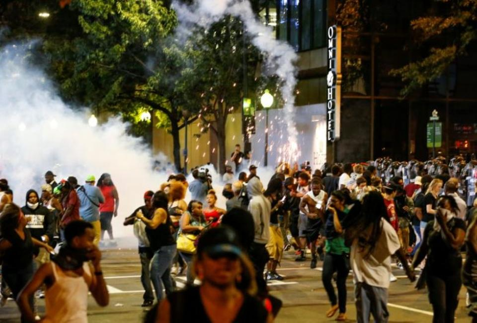 People run from flash-bang grenades in uptown Charlotte, NC during a protest of the police shooting of Keith Scott, in Charlotte, North Carolina, US September 21, 2016.