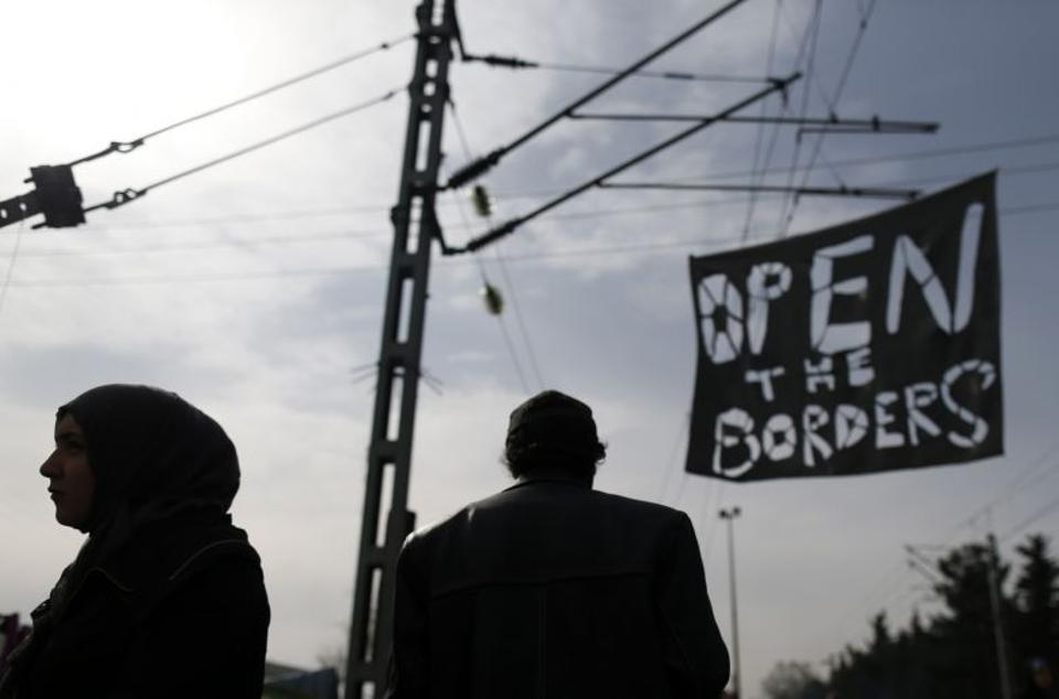 Archive photo shows refugees walking past a banner during a protest demanding the opening of the border between Greece and Macedonia, in the northern Greek border station of Idomeni, Greece, March 22, 2016. (AP Archive)