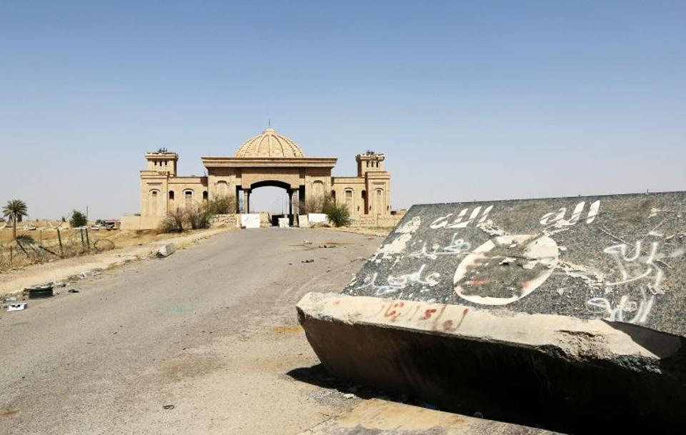 A defaced barrier with DAESH's flag is toppled near the entrance to one of Saddam Hussein's damaged palaces in Tikrit. Civilians have been trickling back into Saddam Hussein's hometown as they look to start anew after a year under DAESH's rule.
