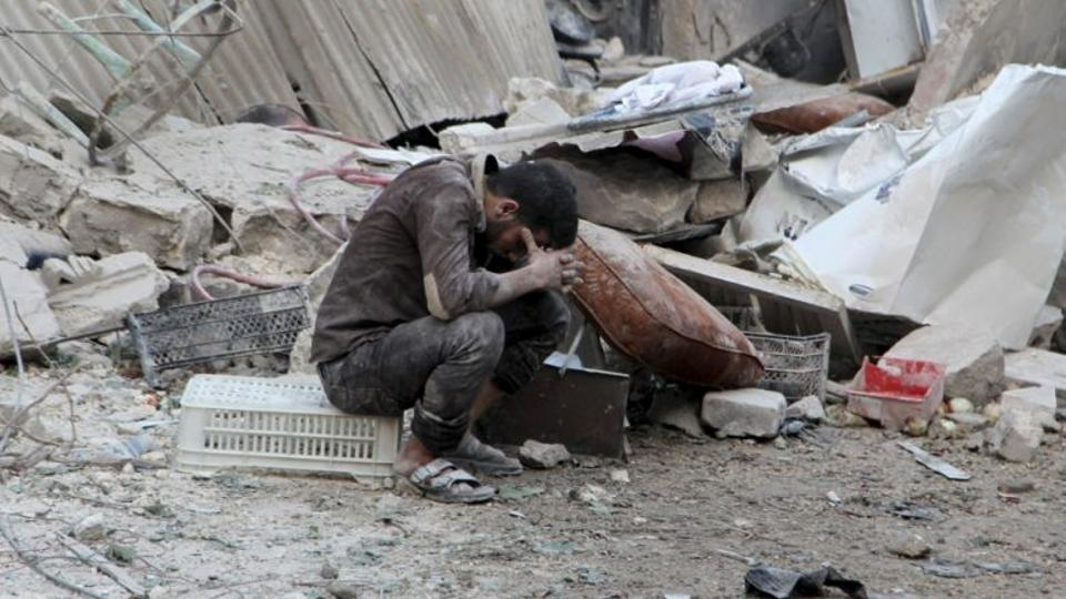 A man reacts amidst damage after an airstrike by forces loyal to Asad regime.