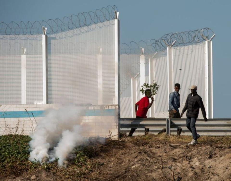 Migrants run away from tear gas during clashes with riot police trying to prevent them from getting into trucks heading to Great Britain, on September 21, 2016 in Calais.