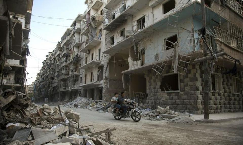 Syrian men ride a motorbike past damaged buildings in the rebel-held Bustan al-Qasr district in eastern Aleppo, on May 4, 2016.