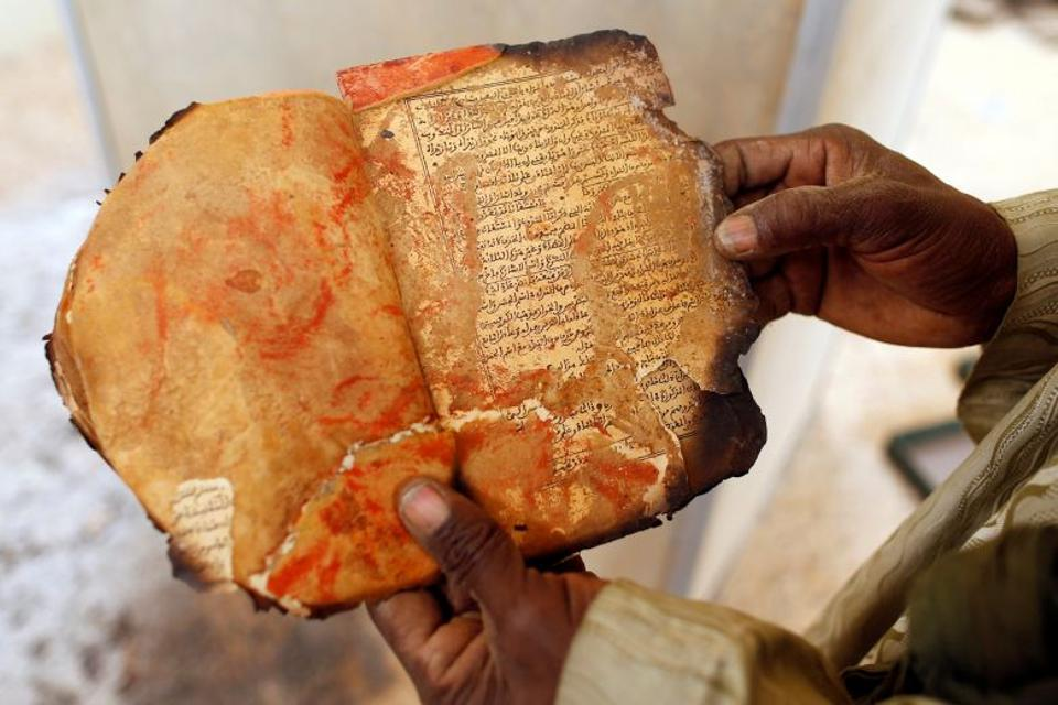 A museum guard displays a burnt ancient manuscript at the Ahmed Baba Institute, or Ahmed Baba Centre for Documentation and Research, in Timbuktu January 31, 2013.