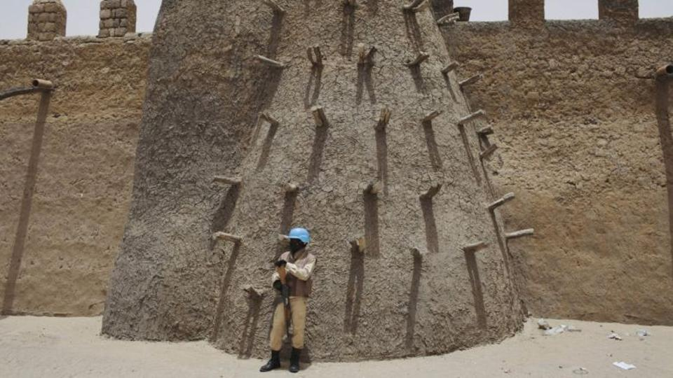 A UN peacekeeper stands near to a historical mosque in Timbuktu.