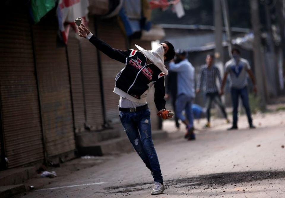 Reacting to a civilian killing, a Kashmiri protester throws a stone at Indian police in Srinagar, the summer capital of Indian-administered Kashmir, on September 13.