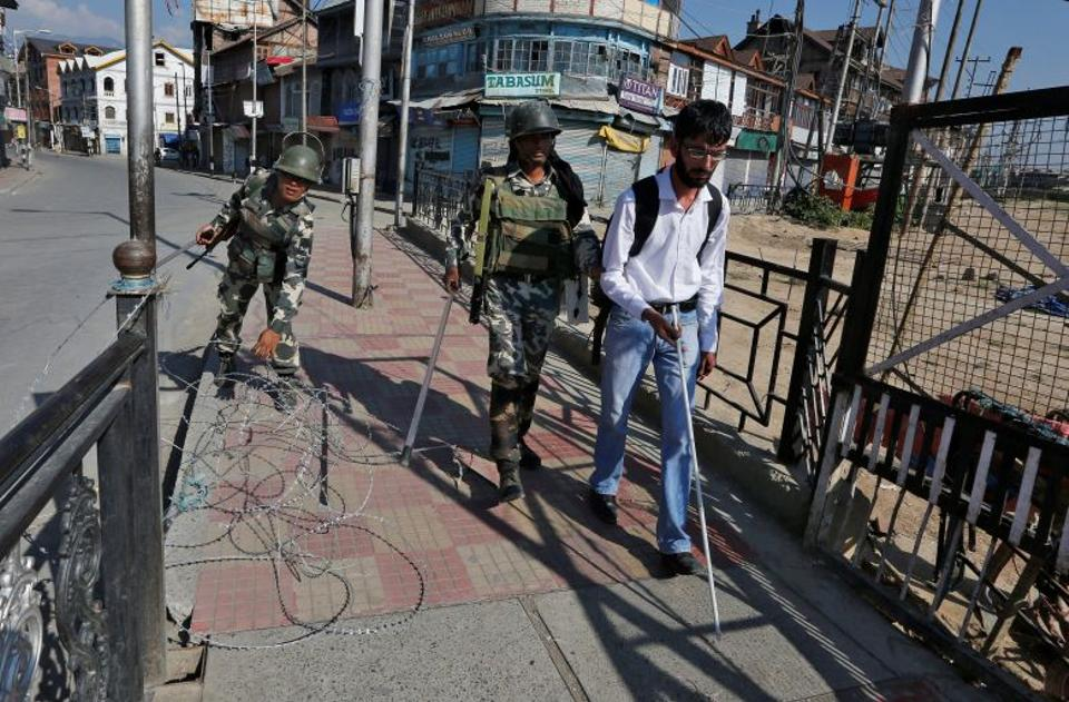 An Indian policeman guides a visually impaired man to cross a concertina wire laid on a bridge during a curfew in Srinagar, September 19, 2016.