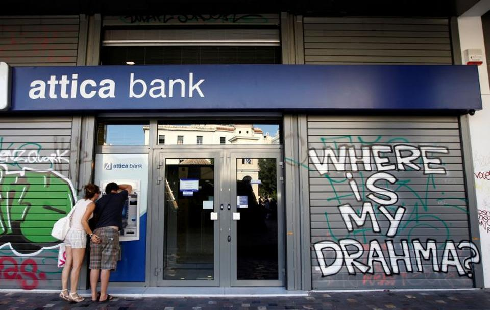 A couple makes a transaction at an ATM outside an Attica bank branch with a graffiti on it in central Athens, Greece August 28, 2012. (Reuters)