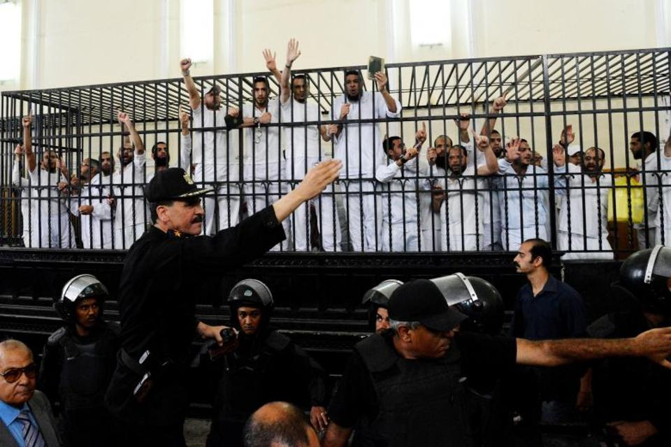 Supporters of the Egyptian Muslim Brotherhood gesture from the defendants cage as they receive sentences including death by hanging for one, life in prison for 13 and 8-15 years for the others following the Arab Spring.