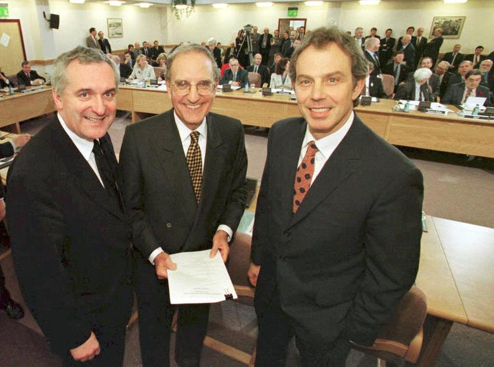 British Prime Minister Tony Blair (R), US Senator George Mitchell (C) and Irish Prime Minister Bertie Ahern (L) smile after they sign a historic agreement for peace in Northern Ireland, ending a 30-year conflict, April 10, 1998