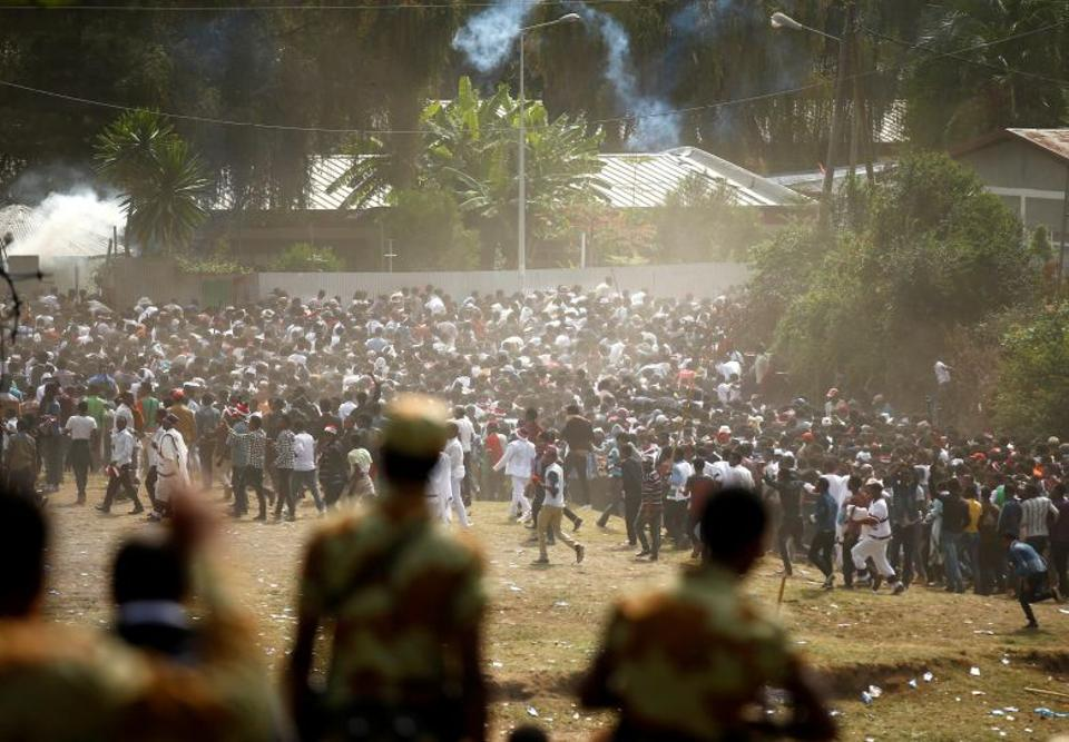 Protesters run from tear gas launched by security personnel.