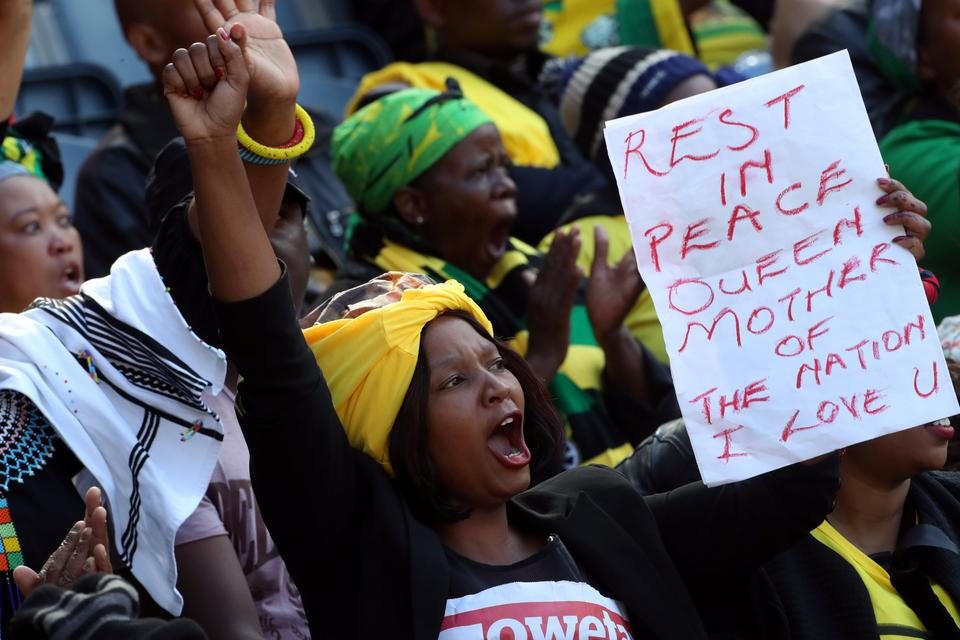 A woman holds a banner and cheers during eulogies at Winnie Madikizela-Mandela's funeral in Orlando stadium in Soweto, South Africa, April 14, 2018.