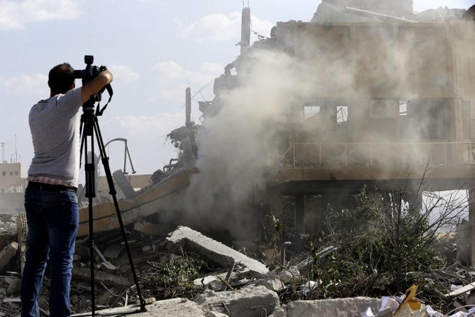 A journalist films the wreckage of a building described as part of the Scientific Studies and Research Centre (SSRC) compound in the Barzeh district, north of Damascus, during a press tour organised by the Syrian regime, on April 14, 2018.