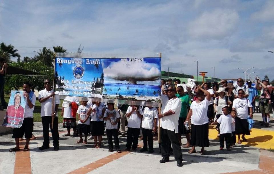 Marshall Islanders from nuclear weapons test-damaged Rongelap Atoll march while holding banners marking the 60th anniversary of the Bravo hydrogen bomb test at Bikini Atoll, in Majuro, in March 2014