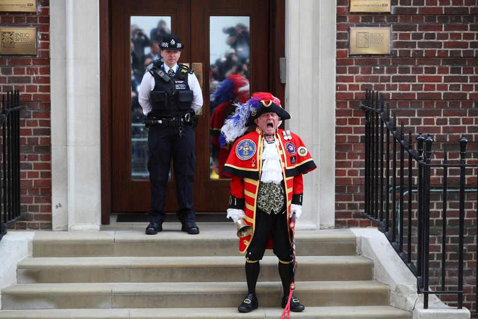 A man dressed as a town crier shouts outside the Lindo Wing of St Mary's Hospital after Britain's Catherine, the Duchess of Cambridge, gave birth to a son, in London, on April 23, 2018.