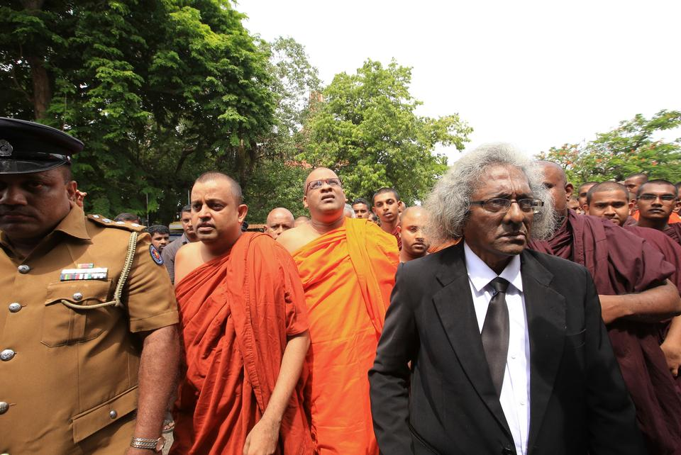 Sri Lankan Buddhist monk Galagoda Aththe Gnanasara, (centre) wearing spectacles, leaves with his lawyers and supporters after obtaining bail following his surrender to a magistrate in Colombo, Sri Lanka on June 21, 2017. (AP Photo/Tharaka Basnayaka)