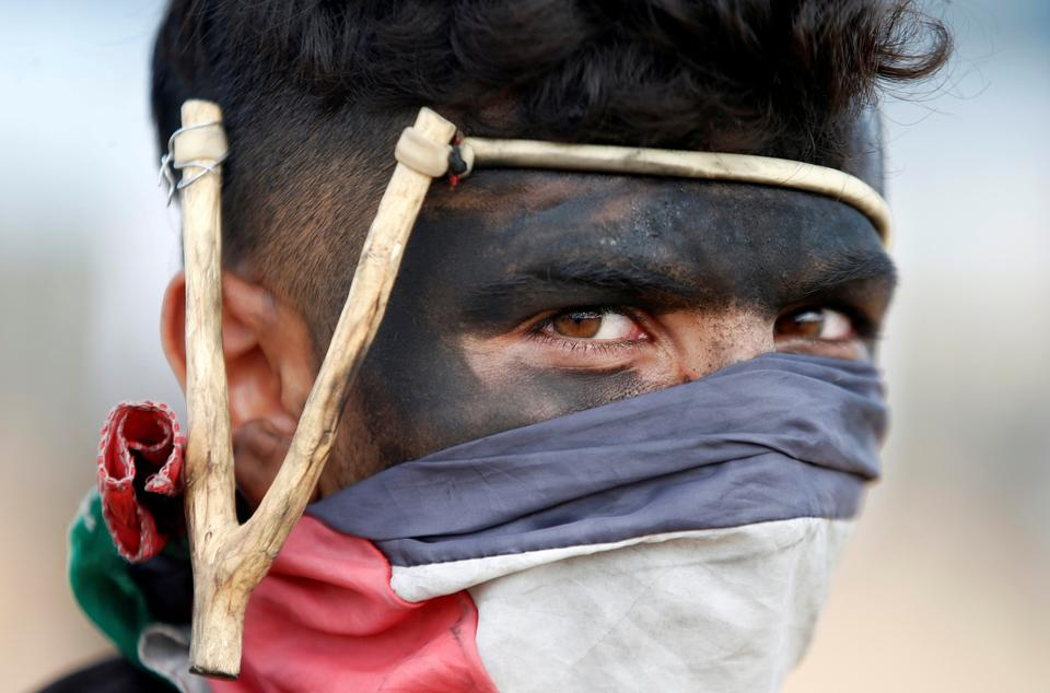 Palestinian demonstrator with a slingshot looks on during a protest against U.S. embassy move to Jerusalem and ahead of the 70th anniversary of Nakba, at the Israel-Gaza border.