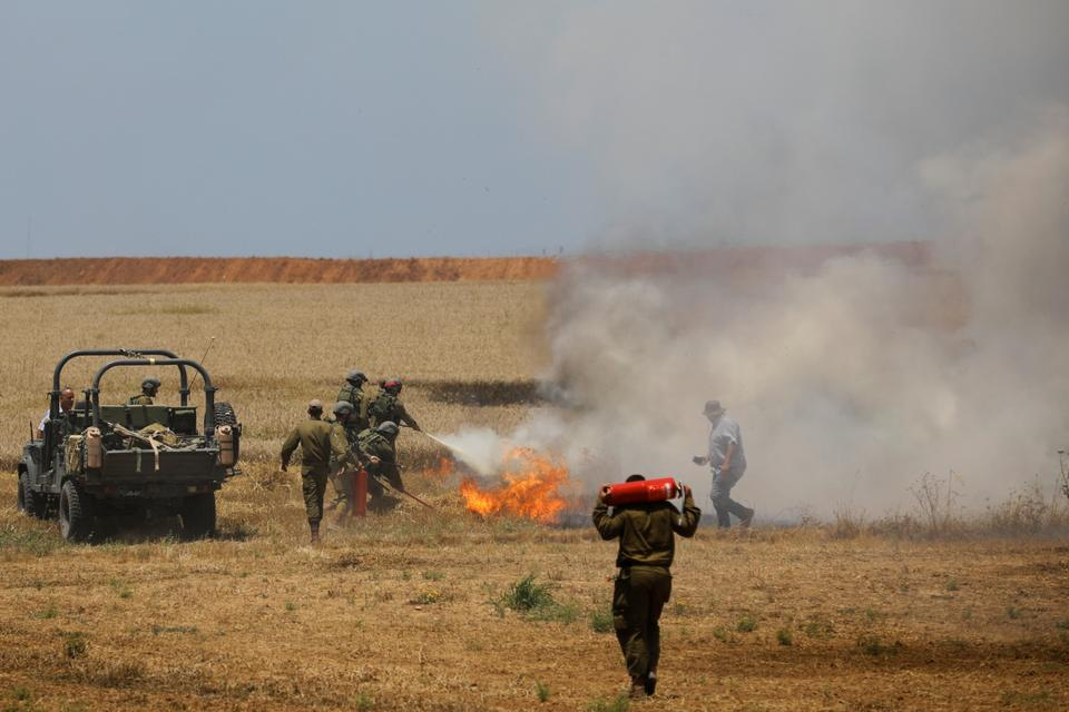 Israeli soldiers attempt to extinguish a fire in a field on the Israeli side of the border fence between Israel and Gaza near kibbutz Mefalsim.