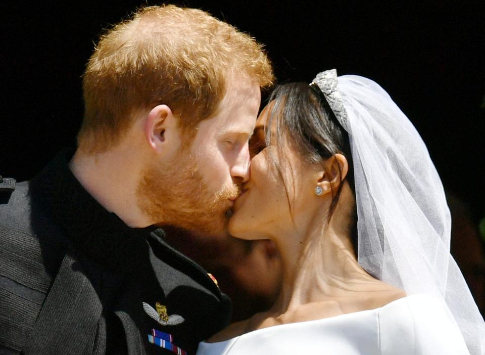 Prince Harry and Meghan Markle kiss on the steps of St George's Chapel in Windsor Castle after their wedding in Windsor, Britain, on May 19, 2018.