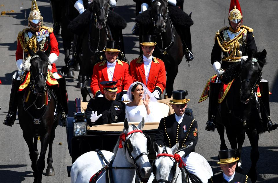 Prince Harry and his wife Meghan Markle wave as they ride a horse-drawn carriage after their wedding ceremony at St George's Chapel in Windsor, Britain, on May 19, 2018.
