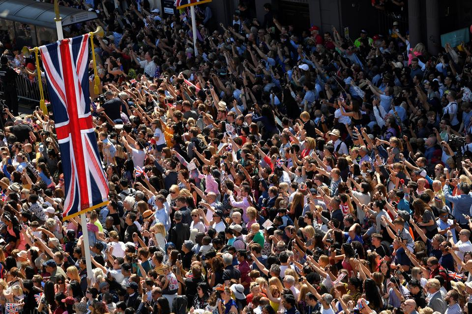 Fans cheer as Britain's Prince Harry and his wife Meghan ride a horse-drawn carriage after their wedding ceremony at St George's Chapel in Windsor Castle in Windsor, Britain, on May 19, 2018.