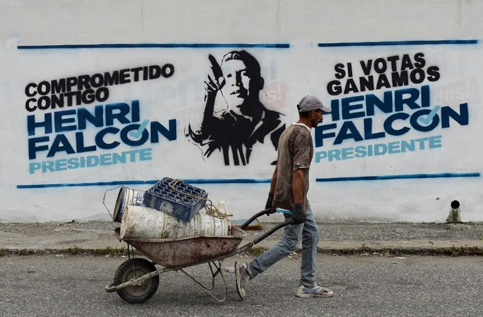 A worker passes by electoral propaganda of Venezuelan opposition presidential candidate Henri Falcon, in Barquisimeto, Venezuela, on May 19, 2018 on the eve of the country's presidential election. Venezuela holds presidential elections on May 20, in which Maduro is seeking a second six-year term.