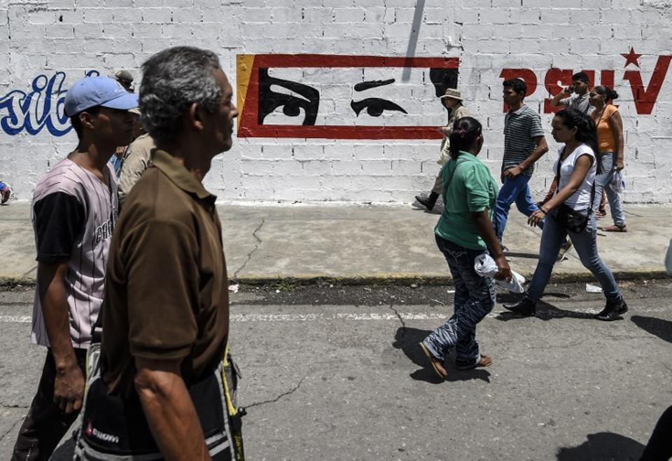 People pass by a graffiti depicting the eyes of late president Hugo Chavez, during a campaign rally by Venezuelan President Nicolas Maduro, in Charallave, about 65 km from Caracas, on May 15, 2018.