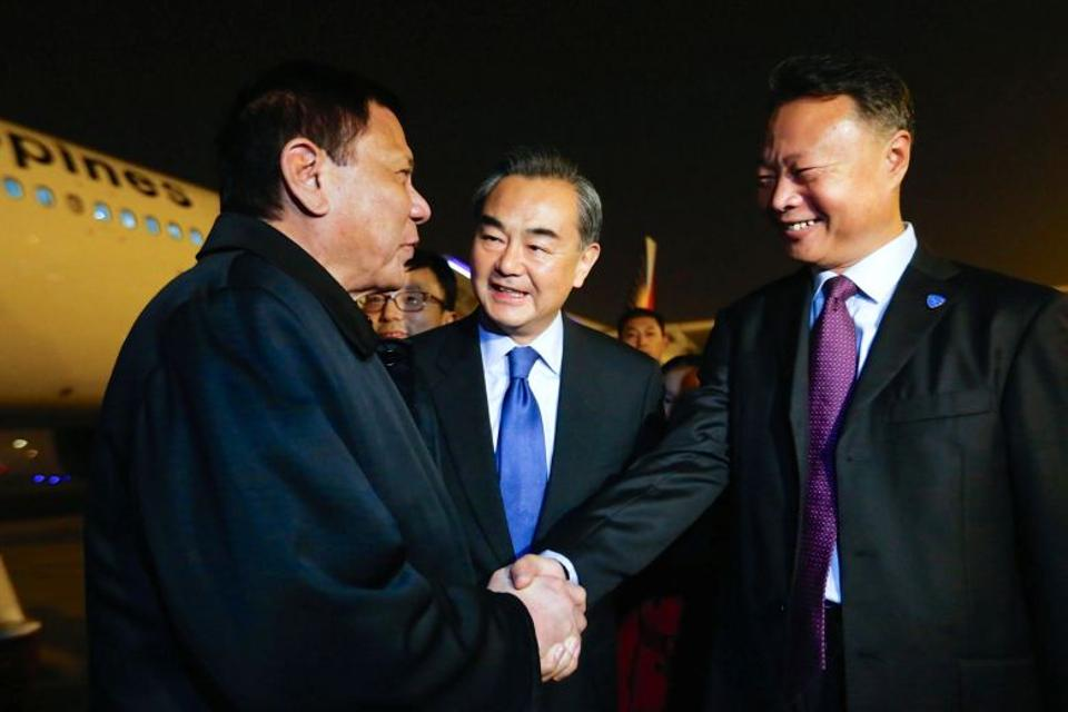 President of the Philippines Rodrigo Duterte (L) shakes hands with Chinese ambassador to the Philippines Zhao Jianhua (R), as Chinese Foreign Minister Wang Yi (C) looks on, at airport in Beijing, China, October 18, 2016. (Reuters)