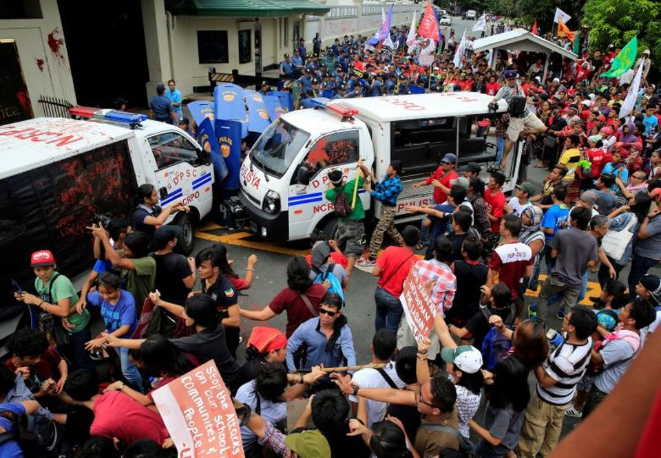 Protesters try to trash a police mobile patrol vehicle as they join various activist and Indigenous People's (IP) groups in a protest against the continuing presence of US troops in the Philippines in front of the US Embassy in metro Manila. (Reuters)