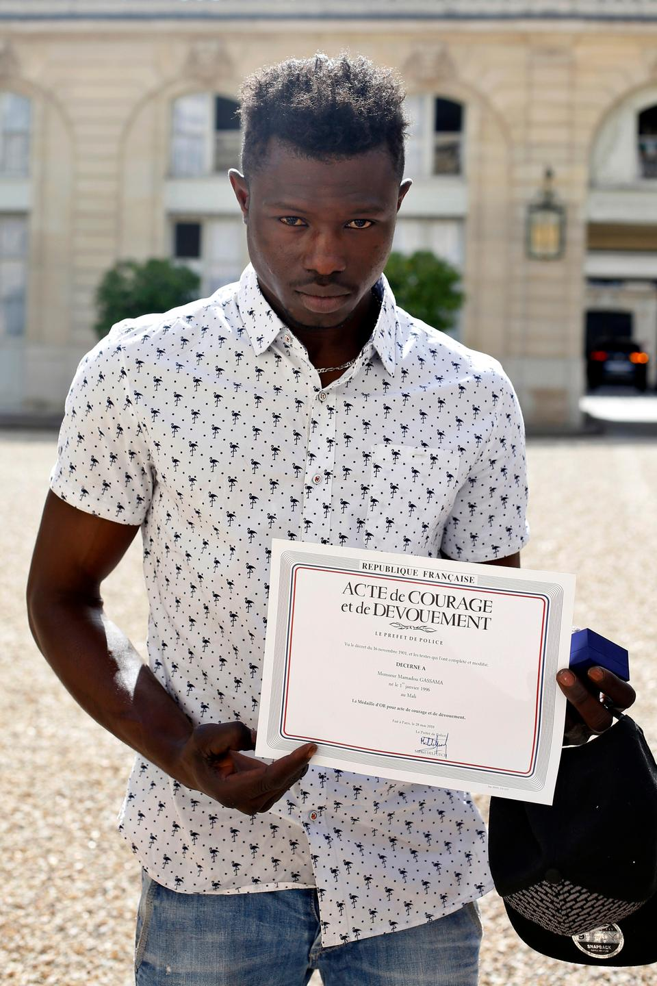 A 22-year old Mamoudou Gassama from Mali displays a certificate of courage and dedication signed by Paris Police Prefect Michel Delpuech as he leaves the presidential Elysee Palace after his meeting with French president in Paris, on May, 28, 2018.