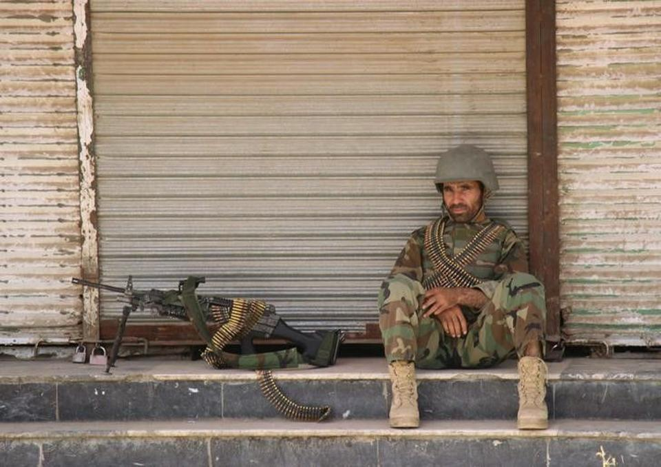 An Afghan National Army (ANA) soldier sits in front of a closed shop in the downtown of Kunduz city, Afghanistan October 3, 2016