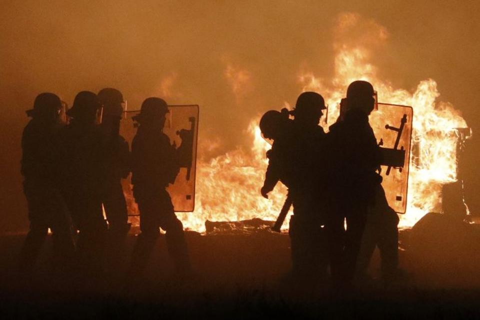 French CRS police are in silhouette as they pass flames on the eve of the evacuation and transfer of refugees to reception centers in France, and the dismantlement of the camp called the